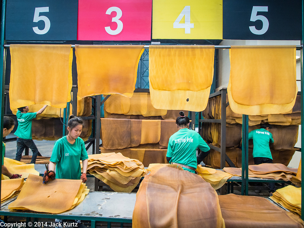 """15 DECEMBER 2014 - KLAENG, RAYONG, THAILAND: Workers sort dried rubber sheets at a quality control station at Supark, a rubber processing plant in Klaeng, Thailand. Thailand is the second leading rubber exporter in the world. In the last two years, the price paid to rubber farmers has plunged from approximately 190 Baht per kilo (about $6.10 US) to 45 Baht per kilo (about $1.20 US). It costs about 65 Baht per kilo to produce rubber ($2.05 US). Prices have plunged 5 percent since September, when rubber was about 52Baht per kilo. Some rubber farmers have taken jobs in the construction trade or in Bangkok to provide for their families during the slump. The Thai government recently announced a """"Rubber Fund"""" to assist small farm owners but said prices won't rebound until production is cut and world demand for rubber picks up.      PHOTO BY JACK KURTZ"""