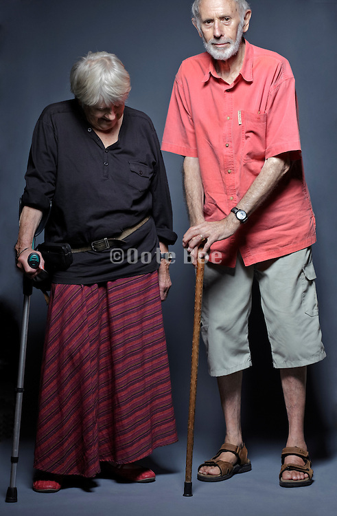 senior couple studio portrait with walking stick and crutch support