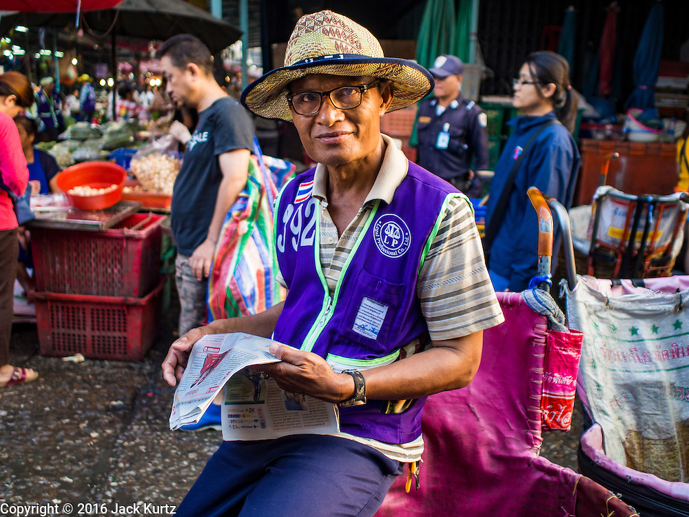 """12 JANUARY 2016 - BANGKOK, THAILAND: A porter reads a newspaper while he waits for customers Khlong Toey Market in Bangkok. Khlong Toey (also called Khlong Toei) Market is one of the largest """"wet markets"""" in Thailand. The market is located in the midst of one of Bangkok's largest slum areas and close to the city's original deep water port. Thousands of people live in the neighboring slum area. Thousands more shop in the sprawling market for fresh fruits and vegetables as well meat, fish and poultry.         PHOTO BY JACK KURTZ"""