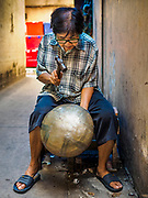 """28 MARCH 2017 - BANGKOK, THAILAND: A woman makes monks' bowls, called """"bat"""" (pronounced with a long """"a"""" as in baat) on Soi Baan Bat in Bangkok. The bowls are made from eight separate pieces of metal said to represent the Buddha's Eightfold Path. The Monk's Bowl Village on Soi Ban Baat in Bangkok is the only surviving one of what were originally three artisan's communities established by Thai King Rama I for the purpose of handcrafting """"baat"""" the ceremonial bowls used by monks as they collect their morning alms. Most monks now use cheaper factory made bowls and the old tradition is dying out. Only six or seven families on Soi Ban Baat still make the bowls by hand. Most of the bowls are now sold to tourists who find their way to hidden alleys in old Bangkok. The small family workshops are only a part of the """"Monk's Bowl Village."""" It is also a thriving residential community of narrow alleyways and sidewalks. The area is also spelled Ban Bat or Baan Bat.          PHOTO BY JACK KURTZ"""