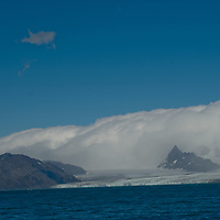Fog rolls over mountains and glaciers of the Allardyce Range above Cumberland Bay, South Georgia, Antarctica.