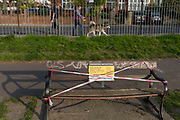 At the beginning of the Easter Bank Holiday weekend, Lambeth council have attached to park benches, notices aimed at the public about restrictions that the UK government's have imposed during the Coronavirus pandemic lockdown, now at the end of its second week, in Ruskin Park, a south London green space, on 9th April, in London, England.