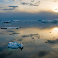 The stunning sunset is reflected in mirror-like water near the Lemaire Channel in Antarctica.