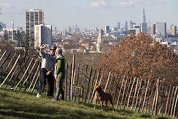 © Licensed to London News Pictures. 26/02/2021. London, UK. Members of the public take a selfie in front of the London skyline in a sunny Greenwich Park in South East London. The national Lockdown is expected to begin to be lifted on the 8th of March with pupils returning to schools and two members of different households allowed to meet outdoors. Photo credit: George Cracknell Wright/LNP