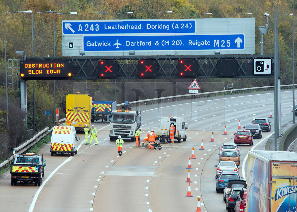 © Licensed to London News Pictures. 14/11/2014. Leatherhead, UK M25 section in Surrey collapses following roadworks<br /> M25. The pothole appeared on the M25 in the early hours of 14th November 2014. Three lanes of the M25 in Surrey have been closed after a section collapsed and left a large pothole, following overnight roadworks. Surrey Police said many vehicles had been left with damaged tyres after the road surface near Leatherhead fell in during heavy rain at about 05:30 GMT.. Photo credit : Stephen Simpson/LNP