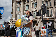 On the day that covid pandemic guidelines for shoppers in England mean that the wearing of face coverings in shops is mandatory, a lady shopper with her face mask on her chin carries party balloons through Oxford Circus , on 24th July 2020, in London, England.