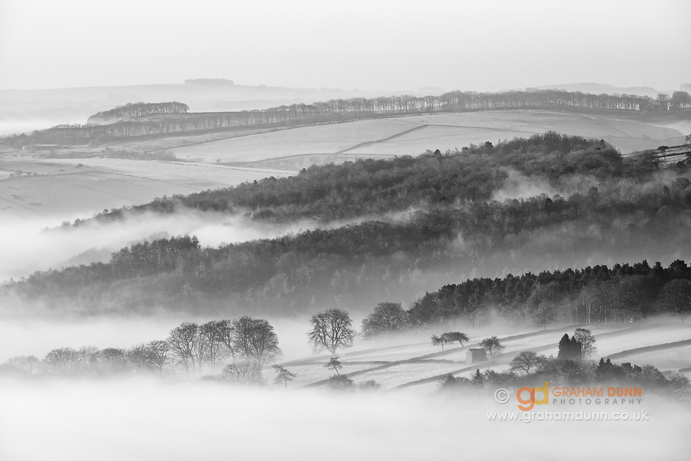 Fingers of mist from the morning's temperature inversion create a beautifully layered landscape above Grindleford and the Derwent Valley in the Peak District National Park. An atmospheric black and white scene in Derbyshire, England, UK.