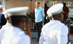 Prince Harry stands to attention during the National Anthem during a visit to Soufriere on the island of St Lucia during the second leg of his Caribbean tour.