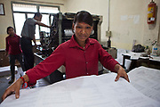 A female Nepalese student sorting paper that has just been printed in the machine behind her in a vocational training centre, Kathmandu, Nepal.  She is studying a one-year course in off-set printing press and once completed, she will hopefully continue to apprenticeship training.  She is an orphan who was rescued by the Friends of Needy Children organization and they are supporting her through her education.  Another female student and male teacher are behind her.