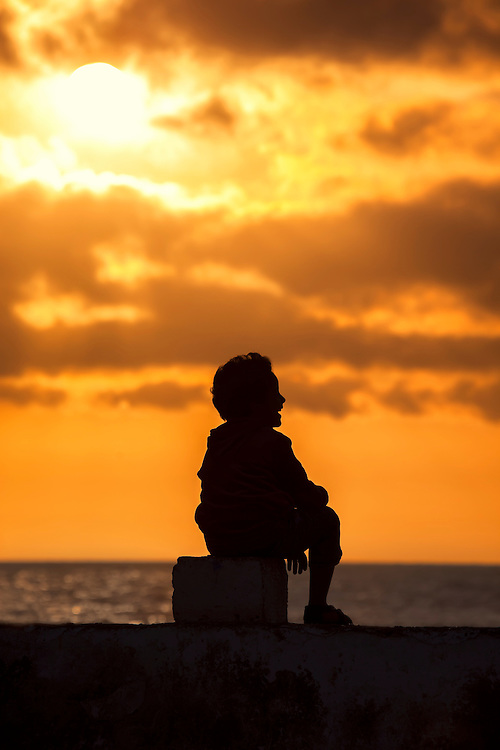 Silhouette of a boy laughing, at sunset in Essaouira.