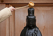 A Japanese woman pours water onto the Arai Kannon statue at Toganji Temple, Sugamo, Tokyo, Japan Friday, March 11th 2011. Sugamo is affectionately known as the old lady Harajuku, in reference to the Mecca for youth fashions in the South of Tokyo, and is a popular place for Tokyo's increasingly aged population. The Arai Kannon statue is a famous religious icon at Togan-ji temple in the heart of Sugamo, where people go to rub the statue with a white cloth in the hopes of curing sickness and ensuring a long, healthy life.