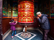 12 MARCH 2017 - KATHMANDU, NEPAL: A Tibetan Buddhist man prays at a prayer wheel at a monastery at Boudhanath Stupa. Boudhanath Stupa in the Bouda section of Kathmandu, is one of the most revered and oldest Buddhist stupas in Nepal. The area has emerged as the center of the Tibetan refugee community in Kathmandu. On full moon nights thousands of Nepali and Tibetan Buddhists come to the stupa and participate in processions around the stupa. The stupa was heavily damaged in the earthquake of 25 April 2015 but has been repaired with the financial assistance of global Buddhist organizations.       PHOTO BY JACK KURTZ