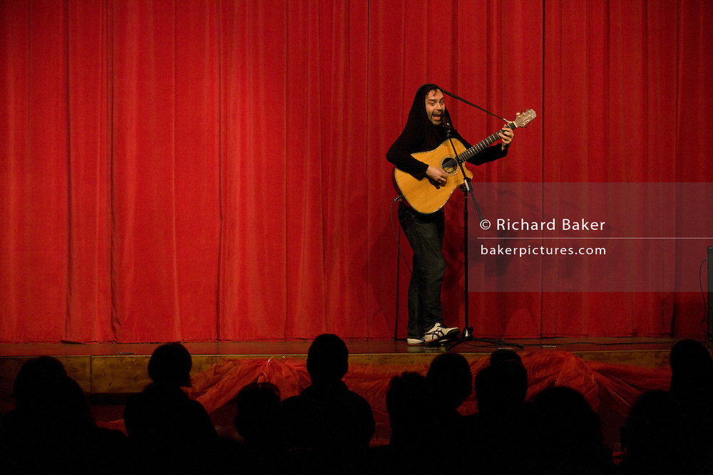 Phil Nichol performs on stage in London.