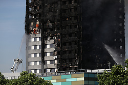Firefighters spray water onto a fire that engulfed the 24-storey Grenfell Tower in west London.