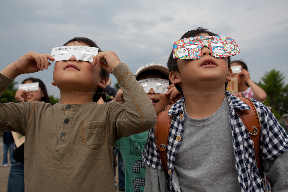 Japanese elementary school children watch a total solar eclipse at 7:32am in Tsukushino Tokyo, Japan. Monday May 21st 2012