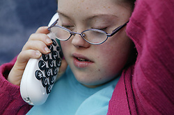 Downs Syndrome teenage girl using a large button telephone,