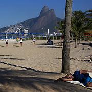 A man sleeps on Ipanema beach as locals play beach volleyball in the background, Rio de Janeiro,  Brazil. 9th July 2010. Photo Tim Clayton..