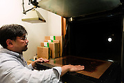 Benrido photographer Katsuhiko Honjo with the atelier's film camera (looking from behind towards the lens). Benrido collotype atelier, Kyoto, Japan, October 9, 2015. The Benrido collotype atelier in Kyoto was founded in 1887 and is the only full-scale commercial collotype atelier in the world. Collotype is a historic photographic printing process that makes use of plates coated in gelatine. It produces prints of unrivalled quality.