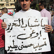 """Sporting an Egyptian national football team hat in a carnival manner, this man shows a banner that appeals to the 'Youth of Tahrir', """"Do not let Mubarak get away!"""""""