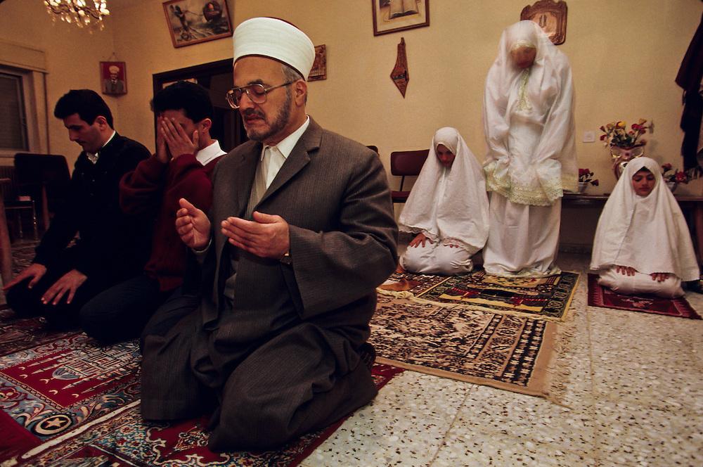 A Muslim family at prayer.
