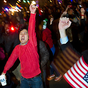 """A crowd celebrates, chanting """"four more years"""" and waving four fingers in the air on U street in Washington DC after Barack Obama was announced the winner of the 2012 presidential elections."""