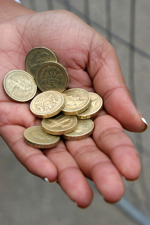 9 British pound coins in the palm of woman's hand.