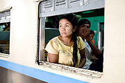 A woman passenger looks out of a carriage window of a train at Mandalay station on 25th May 2016 in Myanmar