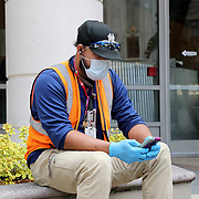 Face mask and gloves are seen on a construction worker as he rests during lunch break on Monday, March 30, 2020 in Orlando, Florida. (Alex Menendez via AP)