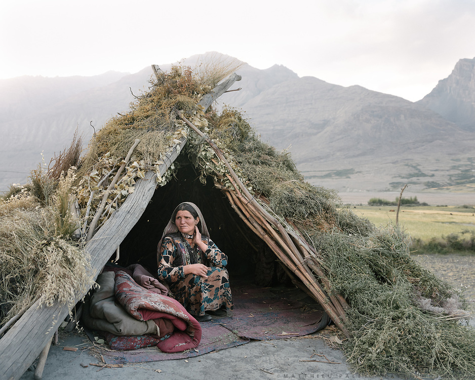 On a roof of her house, a woman takes a break in a tent made of branches and sometimes used for the warmer days in summer.<br />