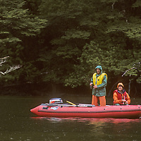During on of many bad weather days, two expedition members fish from a motorized raft in Taraba Sound, a Chilean fjord below Patagonia's previously unexplored Cordillera Sarmiento.  Behind them are southern beech trees.