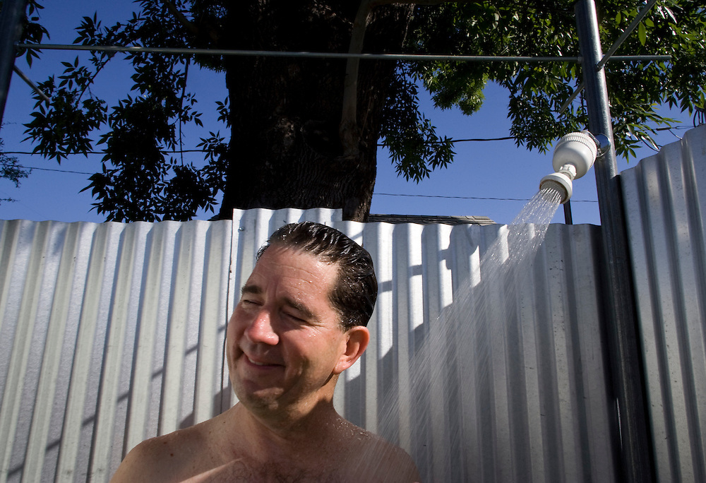 A portrait of Greg Peterson, the Urban Farmer, in his backyard shower. The water is heated by solar panels and Peterson uses environmental-safe soap and shampoo products so the grey water can be used to water his gardens. Since purchasing his home in 1989, Peterson has transformed his third of an acre residential landscape into an edible yard produces over a ton of food per year...