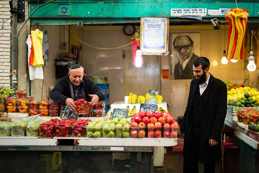 A vendor arranges fruit as he talks with an ultra-Orthodox shopper at the Mahane Yehuda Market, often called 'The Shuk' in Jerusalem, Israel, on February 24, 2016.