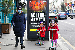 © Licensed to London News Pictures. 18/01/2021. London, UK. Elizabeth wearing a protective face covering, with Wilson aged 5 year old (R) and Ellis aged 2 year old (R) walk past the government's 'Act Like You've Got It' publicity campaign poster in north London, after the mutated variant of the SARS-Cov-2 virus continues to spread around the country. People in England aged 70 and over have started to receive offers of a coronavirus vaccine from today. The government could lift the lockdown in March, after people aged 70 and above have been vaccinated. Every adult in the UK will be offered a first dose of a coronavirus vaccine by September. <br /> <br /> ***Permission Granted***<br /> <br /> Photo credit: Dinendra Haria/LNP