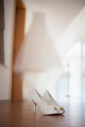 Wedding shoes on the floor with wedding dress in background, Fuerstenfeldbruck, Bavaria, Germany