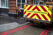 Highway maintenance vehicle looks like it has laid some double red lines with it's wheels, London, UK. Meanwhile a young man texting while outside having a cigarette break.