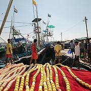 Nepali men working on industrial fishing boats in a harbor.