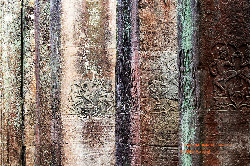 Dancing Through Time: Colourful, intricately carved square vertical columns form a line and each is dominated by dancing female figures, Bayon of Angkor Thom, near to Angkor Wat, Siem Reap Cambodia.