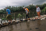 April 28, 2016. CENTRALJAVA-INDONESIA.  <br /> <br /> Every Thursday afternoon, pilgrims go to the cemetery to praying for their family, and passing the only one of broken road because of the abrasion on the side of the coast of the Tambak Lorok Village in Semarang City, Central Java, Indonesia.<br /> Abrasion struck the Tambak Lorok coastal village, Sub-district of Tanjungmas, District North of Semarang, more severe because the land has eroded over 1 kilometer from the shoreline. As a result of this coastal damage caused tidal water entered into the home of locals with a height of between 60 cm to 1 meter, including damaging the cemetery lands on the side of the village. There are at least 22 heads of families in the area were forced to evacuate to a safer place. According to some residents of the Tambak Lorok Village, if not addressed seriously by the government, they believe within one to two years ahead more damage will be even worse than today.<br /> © Aji Styawan/ Exclusivepix Media