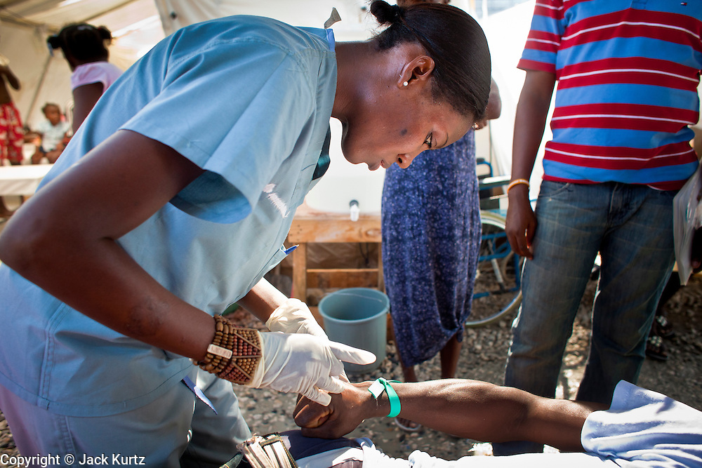 18 NOVEMBER 2010 - PORT-AU-PRINCE, HAITI:  Dr. Juliette Olivier, a Haitian physician with Medecins Sans Frontieres (MSF - Doctors Without Borders) starts an IV on a cholera patient in a MSF cholera stabilization center in Cite Soliel in Port-au-Prince. Cite Soleil, a sprawling slum area in PAP is ground zero for the cholera epidemic in the Haitian capital. An outbreak of cholera in northern Haiti about a month ago has spread across the nation. Tens of thousands of people have been hospitalized and treated for cholera and more than 1,100 have died. Cholera is a water borne illness that causes severe diarrhea and death by dehydration in a matter of hours.   PHOTO BY JACK KURTZ  choleraepidemic