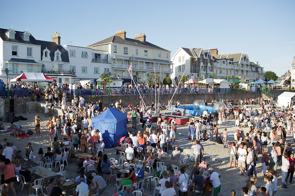Crowds of people at the Havre des Pas summer food festival sitting enjoying food from the stalls or walking around