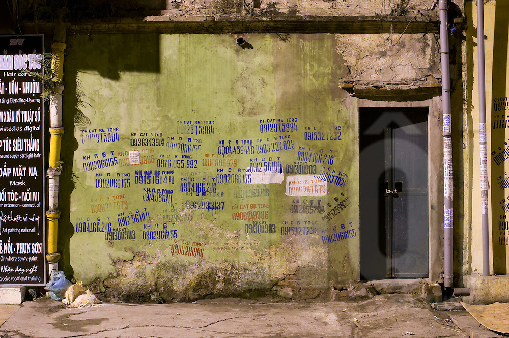 Weathered wall tagged with phone numbers, Hanoi, Vietnam, Southeast Asia, 2009