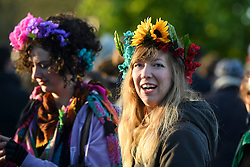 © London News Pictures. 01/05/2016. Oxford, UK.  Two young women wearing flowers in their hair enjoy the May Day day celebrations in the early hours of the morning near Magdalen Bridge in Oxford, Oxfordshire. This year people were again prevented from jumping from the bridge in to the water due to serious injuries sustained at a previous years event . Photo credit: Ben Cawthra/LNP