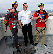 From left, Travis Pastrana and Erik Roner have fun with a security guard as they prepare for base jumping off The Signature at the MGM Grand Hotel & Casino on Wednesday June 1, 2011 in Las Vegas to promote the North American debut of Nitro Circus Live at the MGM Grand Garden Arena on Saturday June 4, 2011. (Jeff Bottari/AP Images for Nitro Circus Live)