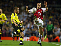 Photograph: Scott Heavey.<br />Arsenal v Aston Villa. FA Barclaycard Premiership match. 27/08/2003.<br />Dennis Bergkamp toes ahead of Olof Mellberg to set up Thierry Henry in the last minute.