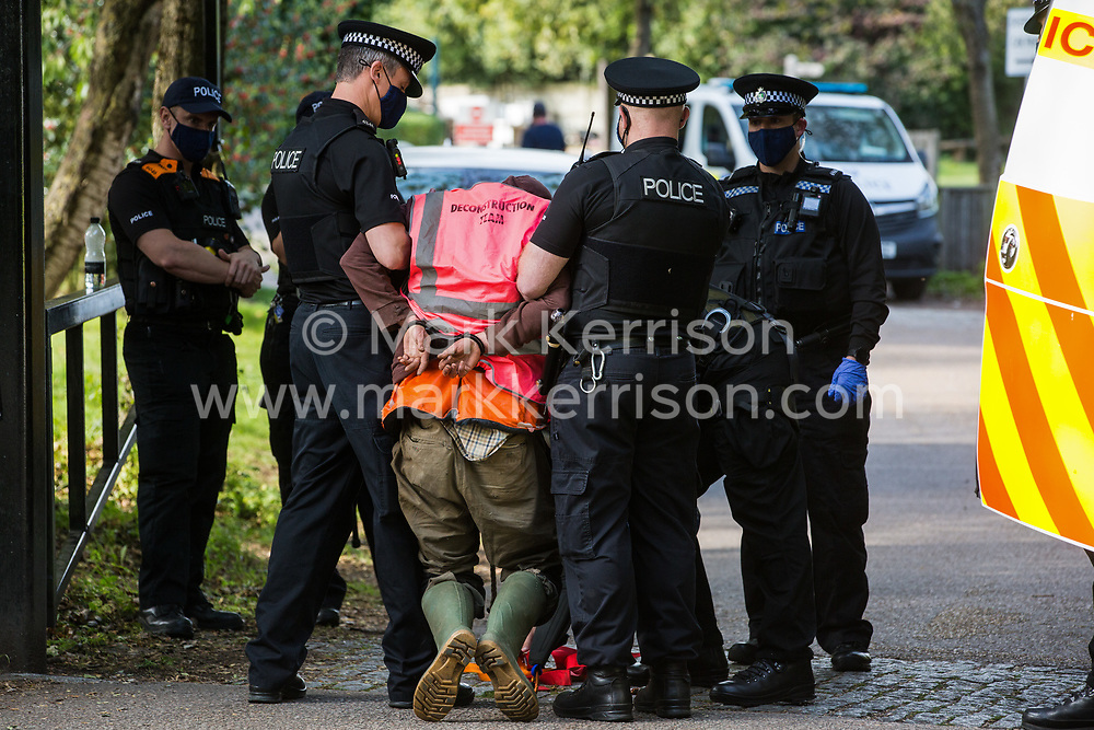 Thames Valley Police officers arrest an anti-HS2 activist who had glued himself to a HGV with a rope around his neck in order to block its passage to works for the HS2 high-speed rail link on 28 September 2020 in Denham, United Kingdom. Environmental activists continue to try to prevent or delay works on the controversial £106bn project for which the construction phase was announced on 4th September from a series of protection camps based along the route of the line between London and Birmingham.