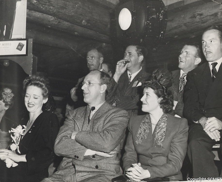 1943 (l to r) Bette Davis, Kay Kyser(arms folded), Mervin LeRoy(with cigar), Gracie Allen, George Burns & Bob Hope watch during the Hollywood Canteen's first birthday ceremonies.