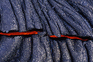 At around 1100 degrees centigrade, molten basalt lava glows  through a crack in the newest land on earth, on the flanks of Kilauea volcano, Hawaii, USA.