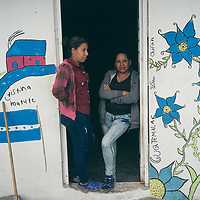 Two women migrants from Central America at the Apizaco migrant shelter, Tlaxcala, Mexico. The women had arrived on the train network called La Bestia. The wall has a mural painted by migrants with emblems from Honduras and Guatemala.