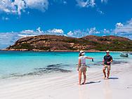 Lucky Beach, Esperance, Australia--February 9, 2018. A woman is handing a mobile phone to her companion as he walks toward her on the stunningly beaut