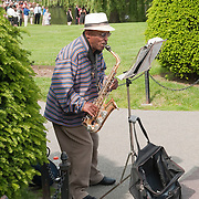 """Street musician Markeety """"Cowboy"""" Tate playing saxaphone in Boston Public Garden on a spring day."""